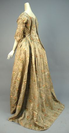 Side view, robe à la francaise, France, 1774-1793. Cream silk open robe having silver metallic stripe and polychrome silk floral brocade, elbow length sleeve trimmed in knotted net with silk ribbon and tambour embroidered floral applique, neckline, bodice and skirt trimmed in metallic lace and ribbon flowers, self buttons on bodice back for tying up skirt, skirt having front panels appliqued with horizontal bands of net, lace and floral embroidery decorated with red, blue and silver foil…