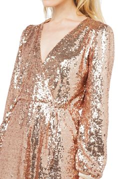 AKIRA's Wild About Tonight Rose Gold Sequin Dress features a draped V-neck, an elasticized waist, a wrap skirt, and long sleeves with elasticized cuffs. Free standard U.S. shipping $75+.
