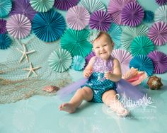 Mermaid 1st Birthday Cake Smash Photo and Props by Lightwork Photography, teal, turquoise, purple, lavender, lace crown with seashells, fish netting, paper fans, rosettes, pinwheels, outfit from ShopBelleThreads on etsy.com