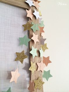 A sweet tiny stars paper garland featuring textured peach, mints, white and glitter gold cardstock measuring approximately 3 metres