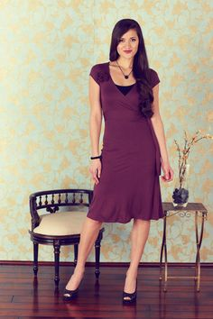 """Modest: """"Kristy"""" Modest Wrap Dress in Plum. The Kristy is a twist on a traditional wrap dress. Allows for a bit more coverage than a conventional full-wrap. The skirt does not wrap, so you don't have to worry about the skirt opening up or falling to the side when you sit. The short sleeve allows your eye to focus on the stunning flower detail on the right shoulder. The Kristy will allow you to feel comfortable while looking classy. $44.99 http://www.jenclothing.com/mi-7014-kristy-plum.html"""