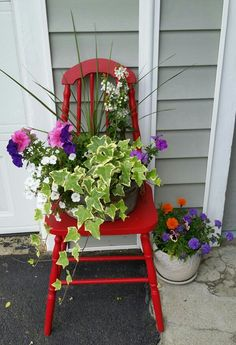 My red chair flower garden. The old broken chair was going to be thrown out. My husband repaired it, and I painted it. Now it looks charming next to our garage! :)