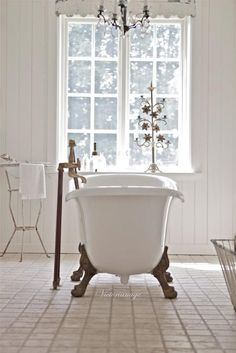 Sweet vintage style white bathroom with claw foot bath