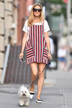 Walk The Line - Olivia Palermo layered her apron dress over a plain white tee, finishing her look with Jimmy Choo flats and a coordinating pop-red manicure. Maltese Terrier Mr Butler undoubtedly approves.