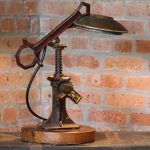 Lamp made from an old vintage car jack, chevy hub cap and a fireman's tool sitting on a heart pine base.  - See more at: http://vintagevaultco.com/shop/piston-rod-rustic-lamp/#sthash.Dk2FESWG.dpuf