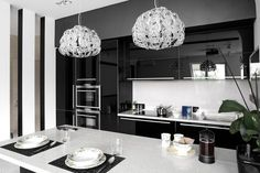 Modern black and white kitchen with dual crystal pendant lights, white counter tops, and black high gloss laminate cabinets.