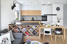 Salon z kuchnią i jadalnią to jedna, wspólna strefa w mieszkaniu. Dzięki wyburzeniu ścianki oddzielającej kuchnię od salonu, powstała otwarta przestrzeń dzienna i w mieszkaniu mogła pojawić się wyspa. Półki w półwyspie nawiązują do geometrii na gresie- płytki swoim wzorem zachwyciły właścicieli już w sklepie.