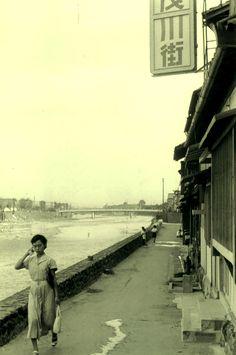 A woman walking alongside the river, Kyoto, Japan, 1955, photograph by Kansuke Yamamoto.