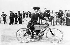 """Mme Jolivet, sportwoman de la première heure sur une bicyclette à pétrole Pécourt, au km lancé de Deauville en 1902. Son mari courait pour la même marque qui fut l'une des premières en France à utiliser le moteur adaptable Z.L. Hélas, le 31 mai 1905 le tribunal prononçait la """"Clôture pour insuffisance d'actif"""" de l'entreprise de """"M. Pécourt, négociant en moteurs, actuellement sans domicile connu""""."""