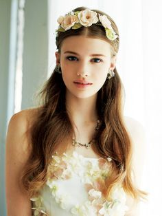 淡いピンクの花がスウィートな花冠。センターパートにした前髪の両サイドをツイストし、ゆるやかに流したダウンヘアの中央に飾って。耳をすっきりと出...