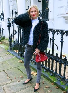 Grey jeans with a furry coat, red bag, and low heels.
