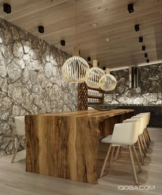 The kitchen and dining combination is indescribably luxurious down to the last detail. Rustic materials give this space a powerful yet organic personality: a one-of-a-kind live edge table invokes the mystique of the forest, and the carefully illuminated stone-clad wall brings to mind images of powerful rivers. Octo lamps and Cut chairs bring the space back to modernity.
