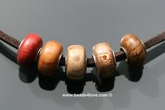 Hand made wooden beads from Tree Wood Studio. All of them with a one piece silver core. They fit on Trollbeads. Pink Ivory, She Oak, Holy Oak, Mahogany, Wych Elm (from left to right)