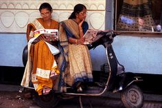 Relaxing on their Scooter and reading the latet gossip in the local newspaper. A daily scene in India, Gujarat. Photo by Boaz.