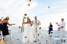 Such an awesome idea for a beach wedding! mini beach balls for the exit or as you go down the aisle!!   photo by www.raeleytham.net