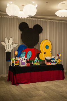 The main table had the cake and favor bags behind it was an 8ft tall Mickey Mouse Clubhouse. Served as a great backdrop for family photos and cake cutting. #thesoireecoweddings#partyflavors