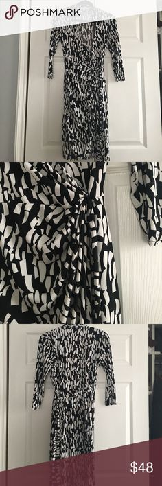 Maggy London Wrap Dress Per owned Maggy London black and white wrap dress. No damages or stains. Beautiful classy works with boots or heels. Very classy may show some signs of wear. Very easy care. Maggy London Dresses Midi