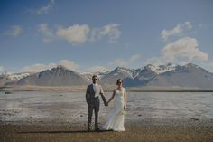 Bride and groom holding hands with a mountain backdrop. Elopement in Borgarnes, Iceland. http://johannahietanen.com/wedding/iceland-wedding-photographer-e-z/