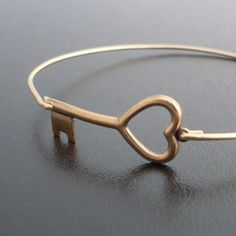 Gold, heart shaped key on a bracelet. A simple gold tone heart shaped key has been transformed into a delicate bangle. Via en.DaWanda.com.