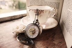 tea cup with pocket watch or flowers or ribbons