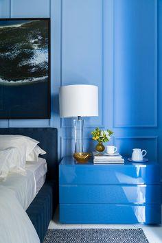 Decoração de quarto em tons de azul na  Quarto Etc. Com criado mudo azul com vasinho e ouro 24k, flores, xícara e abajur.