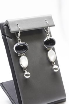 This is a gorgeous set of onyx and mother of pearl drop/dangle earrings. These earrings each feature a large oval onyx stone that is bezel set, as