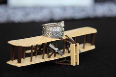 A shot of the rings on one of the airplane decorations - airplane wedding theme - wedding photo  Www.kaitmariephotography.com #aviationweddingdecorations