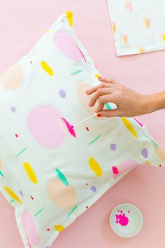 If you're looking for a simple craft project on a rainy afternoon, this is it! All you need is a plain throw pillow cover, a slew of fabric craft paints, @qtips cotton swabs, and have at it. The crazier the merrier in my book! #QtipsHack #sponsor #sugarandcloth