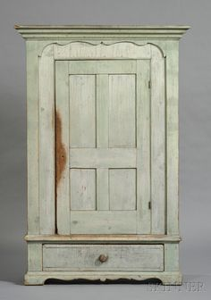 Green-painted Cupboard over Drawer, possibly New England, c. 1840, the cove-molded cornice over a single hinged paneled door opening to shelves, framed by a cutout applied border, the ends with recessed panels with arched tops, original surface, (minor imperfections), ht. 74, case wd. 43 1/4, case dp. 14 in.     Provenance: Estate of Susan Parrish.