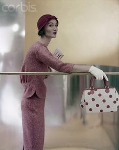 Evelyn Tripp wearing red slim tweed suit, jacket slightly bloused, worn with a close red straw cloche, short white gloves, a polka dot bag. Photographer: Roger Prigent Date Photographed: ca. 1955