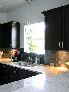 Black cabinets, white countertop, grey subway tile backsplash