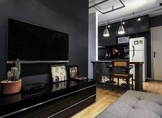 Detalhe da sala de TV enxuta, com parede cinza e rack preto. Em cima do móvel, o vaso com cacto dá graça ao espaço (Foto: Divulgação)