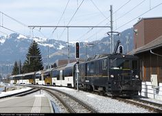 Goldenpass Panoramic Train from Montreux to Zweisimmen over a nice tourist route arrives at Gstaad in the afternoon sun. There are special cars with great windows on this train.