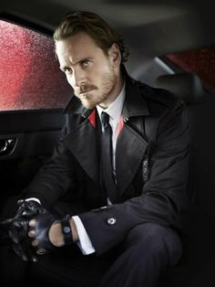 A dapper-looking Michael Fassbender. Love the red background echoing the coat's red details.