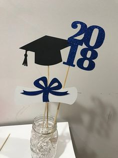 This is a set of 3 graduation stick for centerpiece DIY decorating. The base container is not included. You will receive 1 grad cap , 1 diploma and a 2018 Choose the color you want at checkout. For glitter color , diploma and cap also can be made in Red, pink, gold, silver, blue,