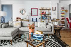 Though the sofa and rug are neutral, pops of color come through accessories such as the artwork, books, and lighting.
