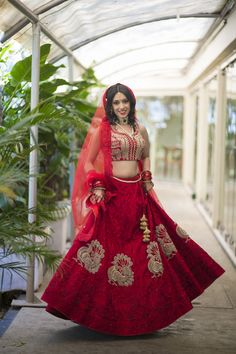 Red Bridal lehenga from Jade , Bustier blouse , silver peacock motif , sparkly bridal lehenga . Bride twirling , green polki choker necklace