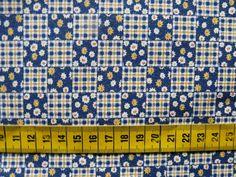 Katoenen stof met een print van kleine vakjes (ca. 1,5 cm) in donkerblauw, wit en geel, met daarin bloempjes en vierkantjes