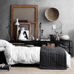 Chambre masculine avec le mur en béton brut, le noir et blanc très graphique du lit. Style et décoration design