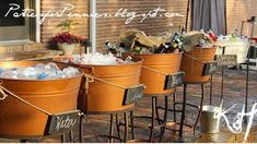 Different tubs filled with ice, labeled for different drinks for wedding reception