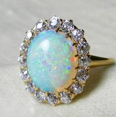 STONE. This oval fire opal is beautiful- maybe a bit too large, but I love the diamonds and kind of like the yellow gold. Makes it warmer- more vintage looking. Antique 3.0 Carat Fine Opal Engagement Ring 1.6 cttw Mine Cut Diamond Australian Opal Ring 18K Rare Blue Black Opal Antique Ring