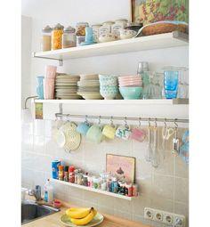 Aqui, as paredes brancas se beneficiaram dos pratos e canecas coloridos