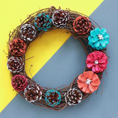 Add a touch of color to your door decor when you make this DIY Painted Pinecone Flower Wreath