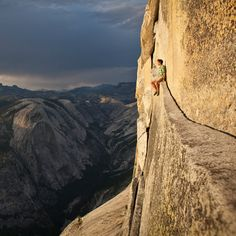 Alex Honnold resting on a narrow ledge, free soloing the 2,000 foot tall northwest face of half dome in Yosemite