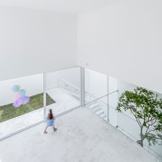 resting atop a stone base, the monolithic exterior obscures the brightly illuminated spaces inside organized around a tree in the atrium.