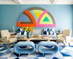Modern, colorful living room with abstract art and two blue stools
