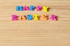 happy easter background greeting with colorful letters on a wooden