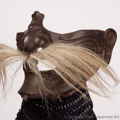 """The signature can be read as """"Yoshiazu of Morioka made this in hard steel for Shimizu"""". The type of this Samurai mask could as well be classified as ressei, due to the fierce expression of the face. Anyway the long moustache are clearly referred to the figure of Okina and to his old age."""