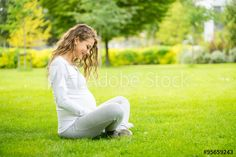 Happy and young pregnant woman in park in summer