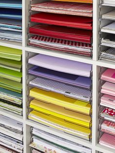 Sheets of 12-inch-by-12-inch scrapbook paper are separated by color in cubbies. Six stacks fit in each cubby, thanks to clear plastic stacki...
